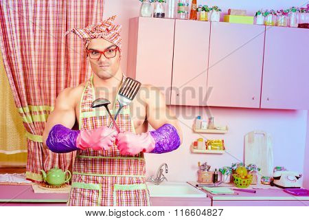 Attractive muscular man in an apron posing with a ladle with expression. Family, love concept. Valentine's day. Women's day.