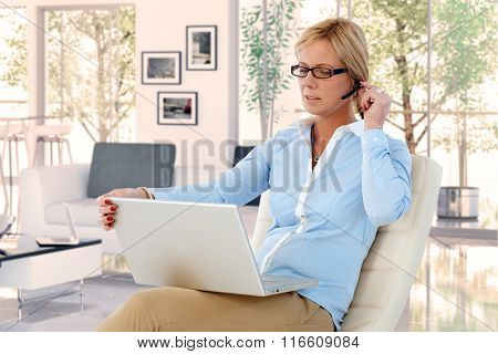 Casual caucasian blonde businesswoman with headset and laptop at home, doing working. Sitting in chair, looking at screen, wearing glasses.