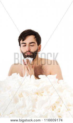 Sick man sneezing into handkerchief.