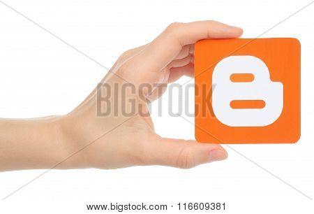 Hand holds Blogger logotype