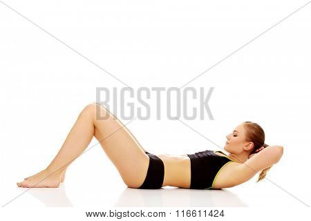 Woman exercising and doing a crunch to work her abs
