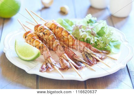 Grilled shrimps on wooden sticks and fresh salad
