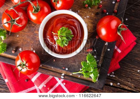 Bowl of tomato sauce and cherry tomatoes on wooden table, close-up.