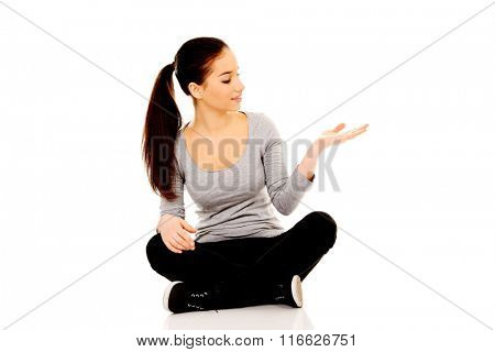 Woman sitting cross legged with open hand.