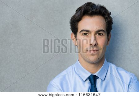 Happy young businessman leaning against grey wall. Portrait of a smirking businessman with blu shirt and tie looking at camera. Closeup of a handsome proud young man smiling with copy space.