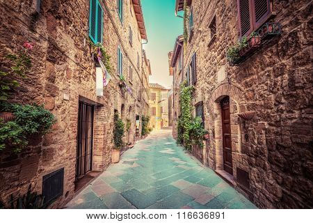 Charming narrow street in an old Italian town of Pienza. Tuscany, Italy. Vintage