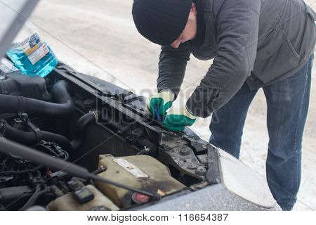 man repairing a car in winter
