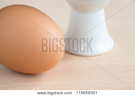 Single brown egg with eggcup on wooden chopping board