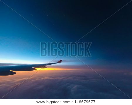 Wing of the plane with cloudy sky on background at sunrise