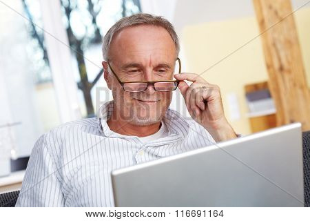 Mature Man With Laptop And Eyeglasses