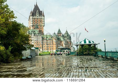 Quebec City Quebec Canada - Sept.9 2015: Chateau Frontenac a landmark hotel towers over the boardwalk beside the St. Lawrence seaway as visitors stroll after a rain shower.