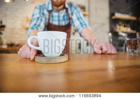 Closeup of white cup of coffee on wooden coster on the table in front of barista