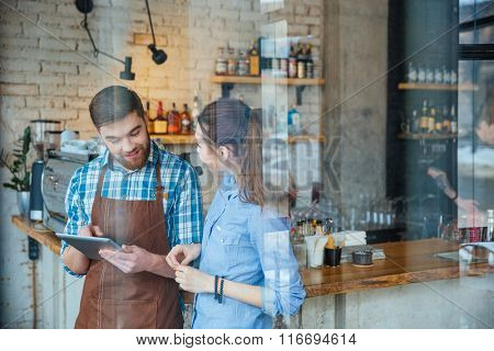 Cheerful bearded young waiter in brown apron talking to young woman and showing information on tablet
