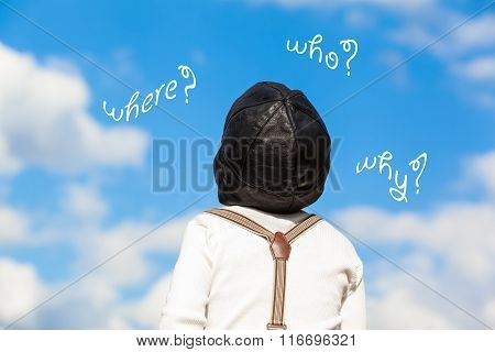 Little boy in vintage clothes (grandad shirt, suspenders, pilot cap) looking up to the blue cloudy sky and ask questions (where, why, who)