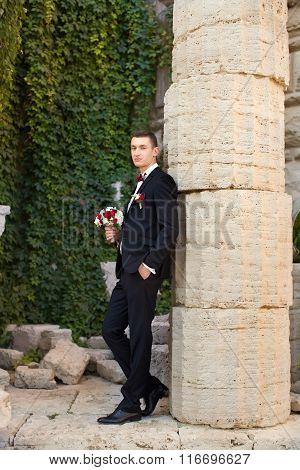 The groom holds a tie and smiles.Portrait of the groom in the park on their wedding day.Rich groom o