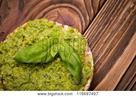 Natural homemade DIY vegan very healthy green pesto made of radish leaves and nutritional yeast flakes on a rice waffle in a glass jar on a wooden table poster
