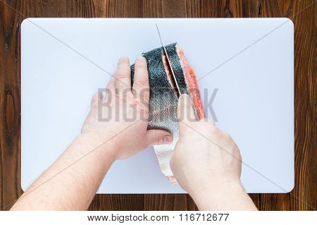 male hands cutting piece of salmon