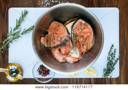marinating steaks of salmon in stainless steel bowl