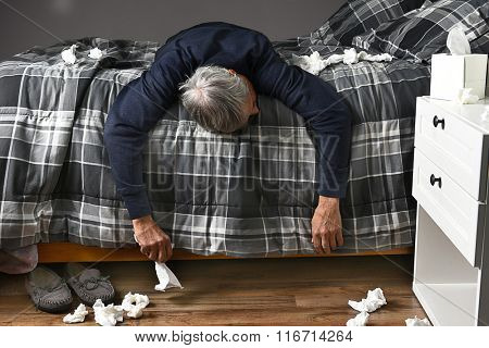 Closeup of a man laying across his bed sick with the flu unable to get up to go to work. Used tissues are strewn about the bed and floor.
