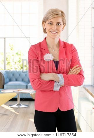 Portrait of confident blonde businesswoman smiling arms crossed.