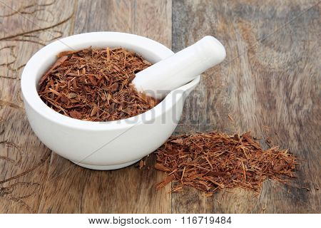 Catuaba bark herb used in natural alternative herbal medicine in a mortar with pestle over old wood background. Used as an aphrodisiac to increase libido.