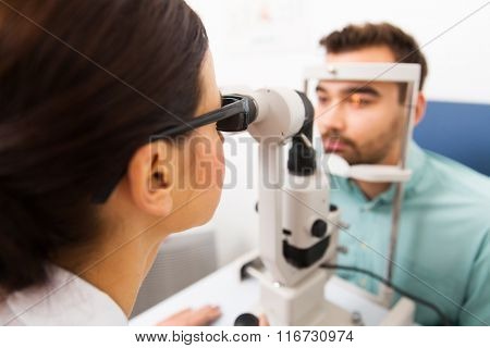 optician with slit lamp and patient at eye clinic