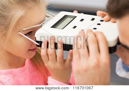 optician with pupillometer and girl at eye clinic