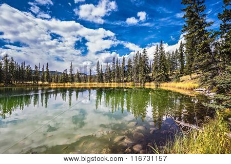 Autumn day in Jasper National Park  in Canada. The small superficial lake is surrounded with coniferous forest. The smooth surface of water reflects the cloudy sky