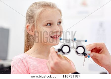 optician with trial frame and girl at clinic