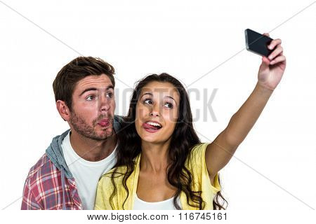 Couple sticking out tongue while taking selfie on white screen