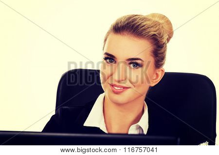 Young smile businesswoman behind the desk, using laptop