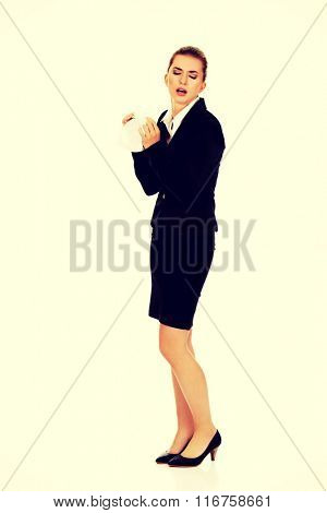 Businesswoman with an allergy sneezing into tissue poster