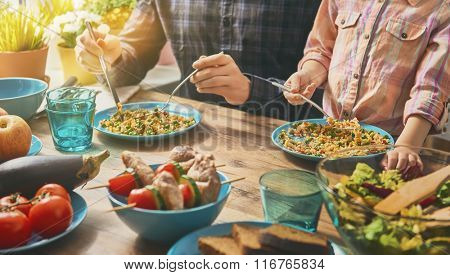 Family having dinner together sitting at the rustic wooden table. Enjoying  family dinner together.