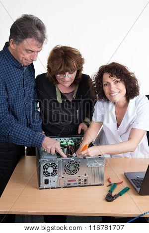 Portrait Of Happy Senior Couple And Pc Repairwoman Fixing Computer