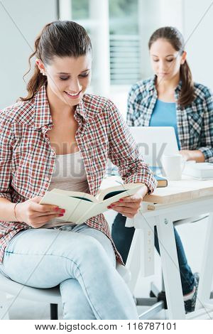 Cute girl at home reading a book and studying her friend is sitting at desk using a laptop