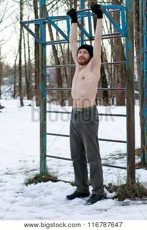 Man In A Black Hat With Naked Torso Doing Street Workout