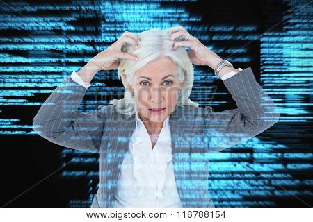 Portrait of stressed businesswoman with hands on head against shiny blue coding on black background