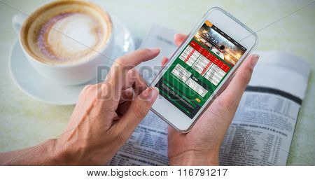 Gambling app screen against man using mobile phone by coffee and newspaper in cafe
