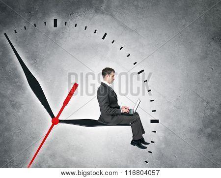Businessman sitting on clockhand