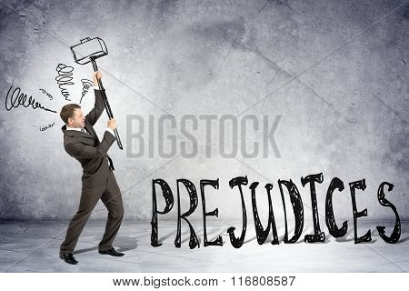 Businessman with hammer and word prejudices