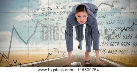 Tradeswoman in sprinting position against stocks and shares