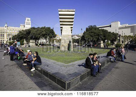 Tourist People Sitting Near Monument To Francesc Macia On The Placa De Catalunya, Barcelona, Spain