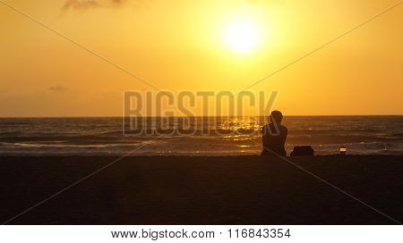 Lonely woman sitting on the beach watching the sunset