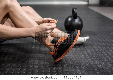 Man tying his shoelaces at crossfit gym