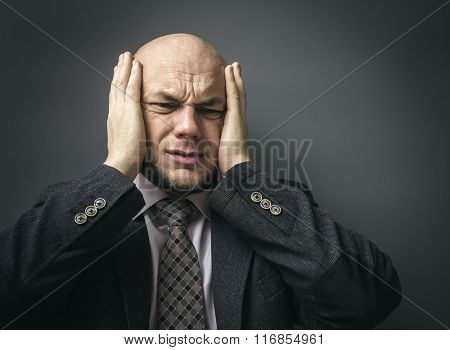 Portrait of an adult man in a business suit on a black background. Headache