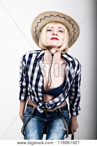 Young beautiful sexy woman in a plaid shirt jeans and a cowboy hat