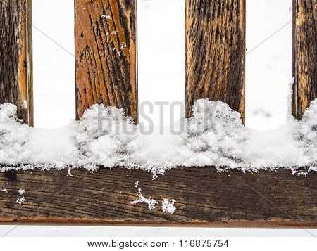 Four wooden rungs or spokes covered with snow
