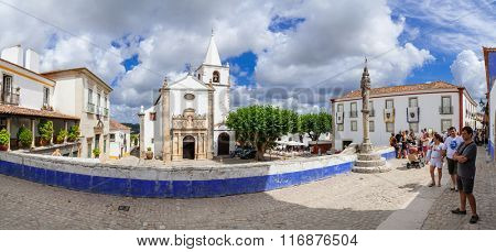 Obidos, Portugal - July, 2015: Santa Maria Church and Town Pillory seen from Direita Street. Obidos is a medieval town inside walls, and very popular among tourists.
