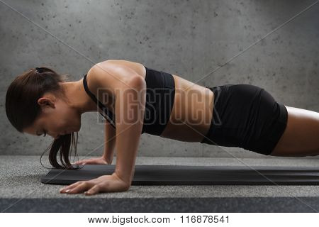 woman doing push-ups in gym poster
