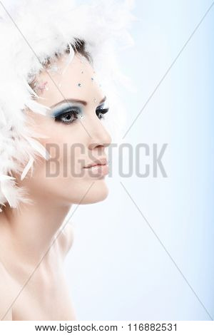 Profile of young winter beauty in white feather cap and fancy makeup with strasses.